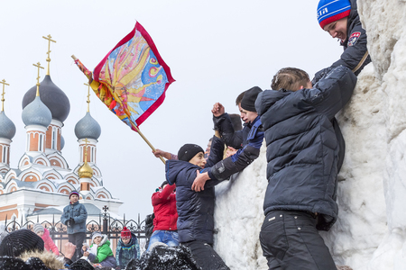 Berdsk, Novosibirsk oblast, Siberia, Russia - February 26, 2017: Russian holiday of farewell to winter. Snow sport games of young people at an Orthodox Church. The storming of a snow fortress