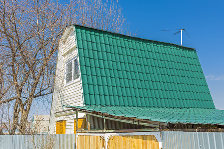 The roof of the country house is covered with metal roofing. The material for the roof Stock Photo