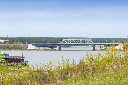 The Berd  river ( tributary of the Ob ), Berdsk, Novosibirsk oblast, Siberia, Russia - may 10, 2017: a view of the pier and the bridge over the river
