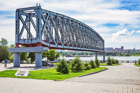 rive: Novosibirsk, Siberia, Russia - July 17, 2017: construction of the first Span of the railway bridge over the Ob river ( Built in 1893-1897 on draft N. A. Belloustogo ) on the waterfront in the Park City home Editorial
