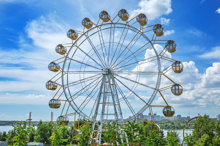 Novosibirsk, Siberia, Russia - July 17, 2017: view of the embankment of the Ob river in the area of the amusement Park and Ferris wheel