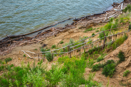 A makeshift ladder of planks and trunks of trees on the steep river Bank leading to the water. The river Ob, Novosibirsk oblast, Siberia, Russia