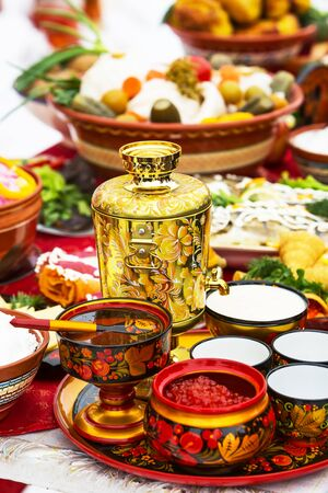 Berdsk, Novosibirsk region, Western Siberia, Russia-March 1, 2020: a Festive table with a painted samovar, honey and red caviar. The Holiday Of Maslenitsa.