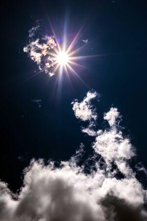 Bright sun and clouds against a dark blue sky Archivio Fotografico