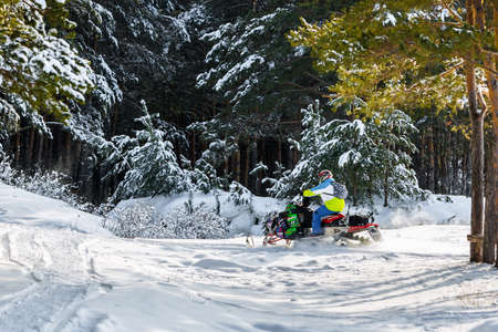 Berdsk, Novosibirsk region, Western Siberia, Russia-February 15, 2020: a Man on a snowmobile rides through a winter forest