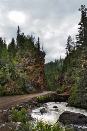 The attraction of Gorny Altai is the Red gate. The road passes through steep rocks red shade, on the river Kibitka. Russia, southern Siberia, Altai Republic, Ulagansky district Archivio Fotografico