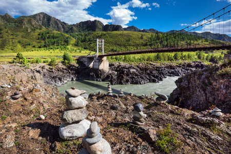 Chemalsky district, Altai Republic, southern Siberia, Russia-August 19, 2020: Oroktoysky automobile suspension bridge over the Katun river surrounded by mountains and stone pyramids