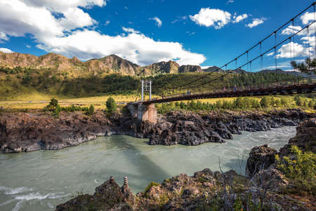 Chemalsky district, Altai Republic, southern Siberia, Russia-August 19, 2020: Oroktoysky automobile suspension bridge on reinforced concrete pillars across the Katun river surrounded by mountains