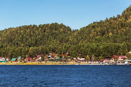 View of the village of Artybash, lake Teletskoye and mountains covered with coniferous taiga. Turochaksky district, Altai Republic, South of Western Siberia, Russia