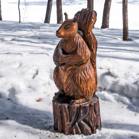 Berdsk, Novosibirsk region, Western Siberia, Russia-April 4, 2021: a wooden figure from a fairy tale-a squirrel with a cedar cone, on the territory of the sanatorium dawn in a snow-covered forest