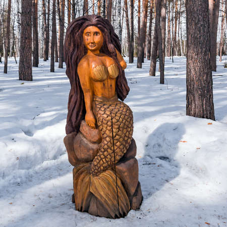 Berdsk, Novosibirsk region, Western Siberia, Russia-April 4, 2021: a wooden figure from a fairy tale-a Mermaid girl, on the territory of the sanatorium dawn in a snow-covered forest