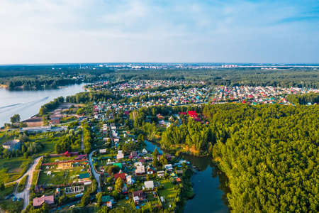 BERDSK, Novosibirsk region, Western Siberia of Russia - July 4, 2021: The coast of the Ob Sea with private houses in garden societies, from a bird's-eye view. The coast of the city of Berdsk.
