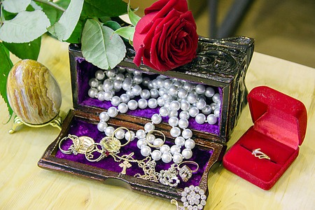 An easter egg, rings, pearl necklace in a jewelry box and a red rose. Stock Photo