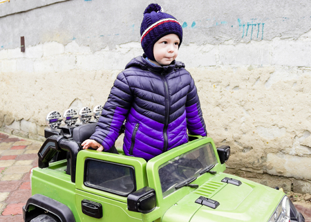 pictured in the photo a beautiful little boy is standing next to a green car Stok Fotoğraf