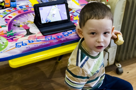 Lipetsk, Russia 03 16 2019 pictured in the photo a little boy is eating a pie and is looking at a tablet Stock Photo