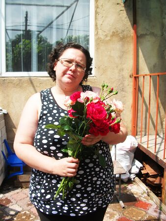 young woman with a bouquet of red and pink roses 写真素材