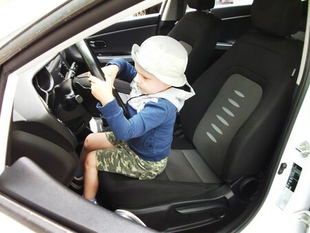 pictured in the photo Portrait of a little smiling blond boy in the car