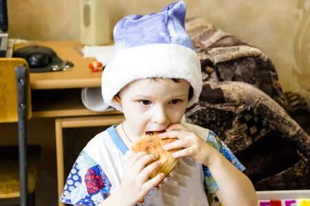 pictured in the photo little boy dressed as Santa Claus eats a pie