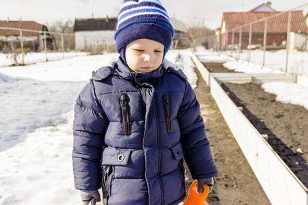 little boy walks in the winter garden 写真素材