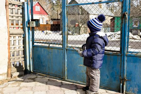 little boy walks in winter plays with a gun 写真素材