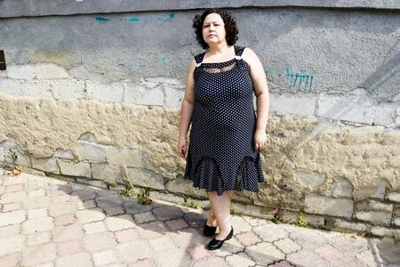 pictured in the photo owerweight woman in a black sundress white polka dots