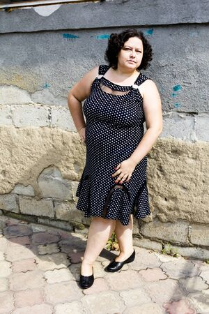 owerweight woman in a black sundress white polka dots