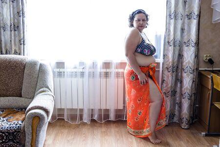 en la foto una mujer regordeta con un traje de baño morado y un pareo naranja