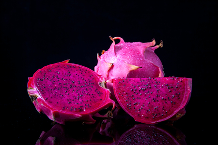 Fresh red dragon fruit with cut dragon fruit and slice on black background