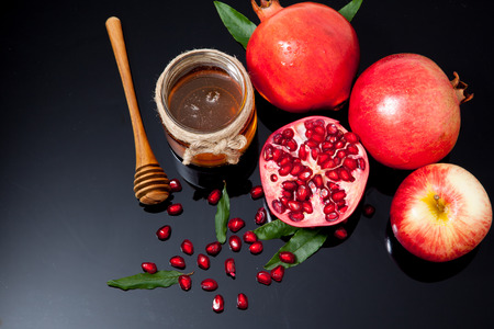 Honey, apple and pomegranate for traditional holiday symbols rosh hashanah (jewesh holiday) on black background Stock Photo
