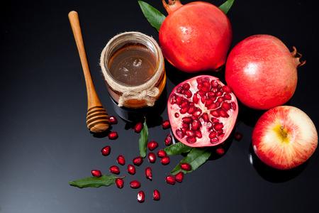Honey, apple and pomegranate for traditional holiday symbols rosh hashanah (jewesh holiday) on black background Standard-Bild