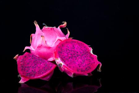 fruta tropical: pitahaya roja fresca con la fruta cortada dragón y segmento sobre fondo negro