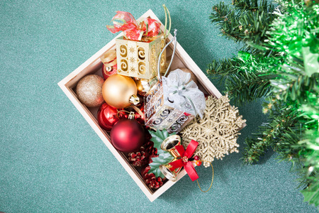Box filled with Christmas decorations on blue background
