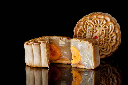 cut up: Two moon cakes with one cut up to show egg yolk for the chinese Mid-Autumn festival on black background Stock Photo