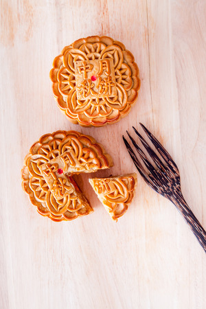 cut up: Two Mooncake with one cut up for the chinese Mid-Autumn festival and wooden fork on woonden bord