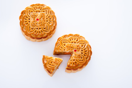 Two mooncake cut up for the chinese Mid-Autumn festival on white background Standard-Bild