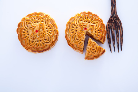 cut up: Two Mooncake with one cut up to show egg yolk for the chinese Mid-Autumn festival and wooden fork on white background