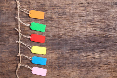 Pack of colourful blank tag, label on wooden table top