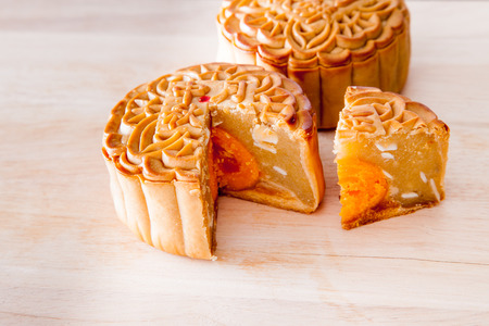 cut up: mooncake cut up to show egg yolk for the chinese Mid-Autumn festival on wooden board