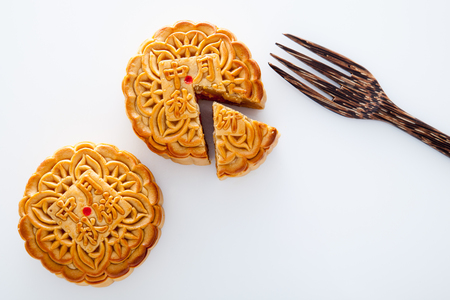 Two moon cakes with one cut up and wooden fork for the chinese Mid-Autumn festival on white background