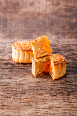 Two mooncake cut up to show egg yolk for the chinese Mid-Autumn festival on wooden table top and wooden background Stock Photo