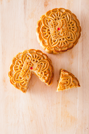 cut up: Two moon cakes with one cut up for the chinese Mid-Autumn festival on wooden cutting board