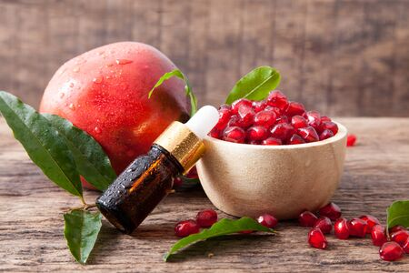 serum bottle or essential oil bottle with fresh pomegranate on wooden table top