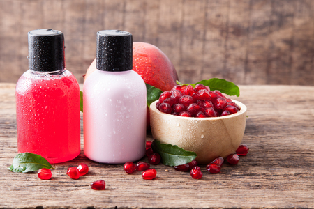 Bottle for shampoo, liquid cleansing soap and conditioner, body lotion with fresh pomegranate on wooden background Reklamní fotografie