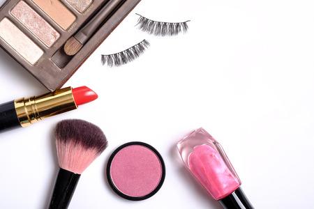 false eyelashes: Beauty background concept, idea for cosmetics make up objects: lipstick, nail polish, eye shadows, false eyelashes, and brush with space for text isolated on white background.