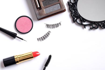 false eyelashes: Beauty background concept, idea for cosmetics make up objects: lipstick, eye shadows, false eyelashes, brush and mascara with space for text isolated on white background. Stock Photo