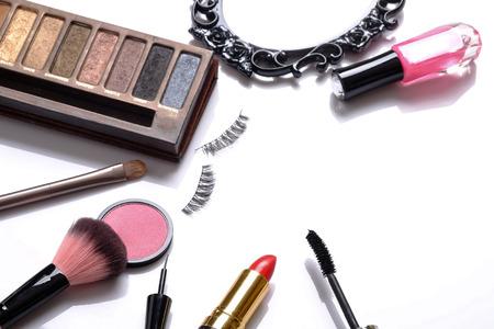 false eyelashes: Beauty background concept, idea for cosmetics make up objects: lipstick, nail polish, eye shadows, false eyelashes, brush and mascara with space for text isolated on white background.