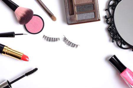 pestaÑas postizas: La belleza del concepto del fondo, la idea para cosméticos constituyen objetos: lápiz labial, esmalte de uñas, sombras de ojos, pestañas postizas, cepillo de rímel y con espacio para el texto aislado en el fondo blanco.