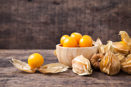 Cape gooseberry in wooden bowl on wooden background Stock Photo