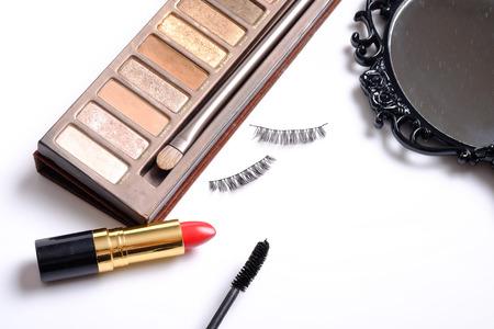 false eyelashes: Beauty background concept, idea for cosmetics make up objects: lipstick, eye shadows, false eyelashes and mascara with space for text isolated on white background.