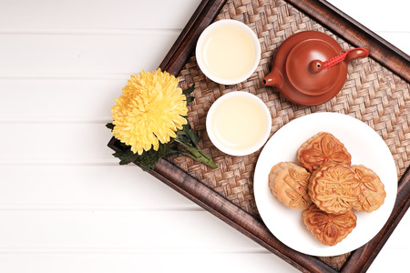 Moon cakes and tea on white table with space for text, background for the Chinese Mid-Autumn festival.